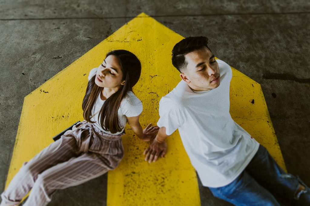 Couple sitting on yellow street arrow facing away from each other