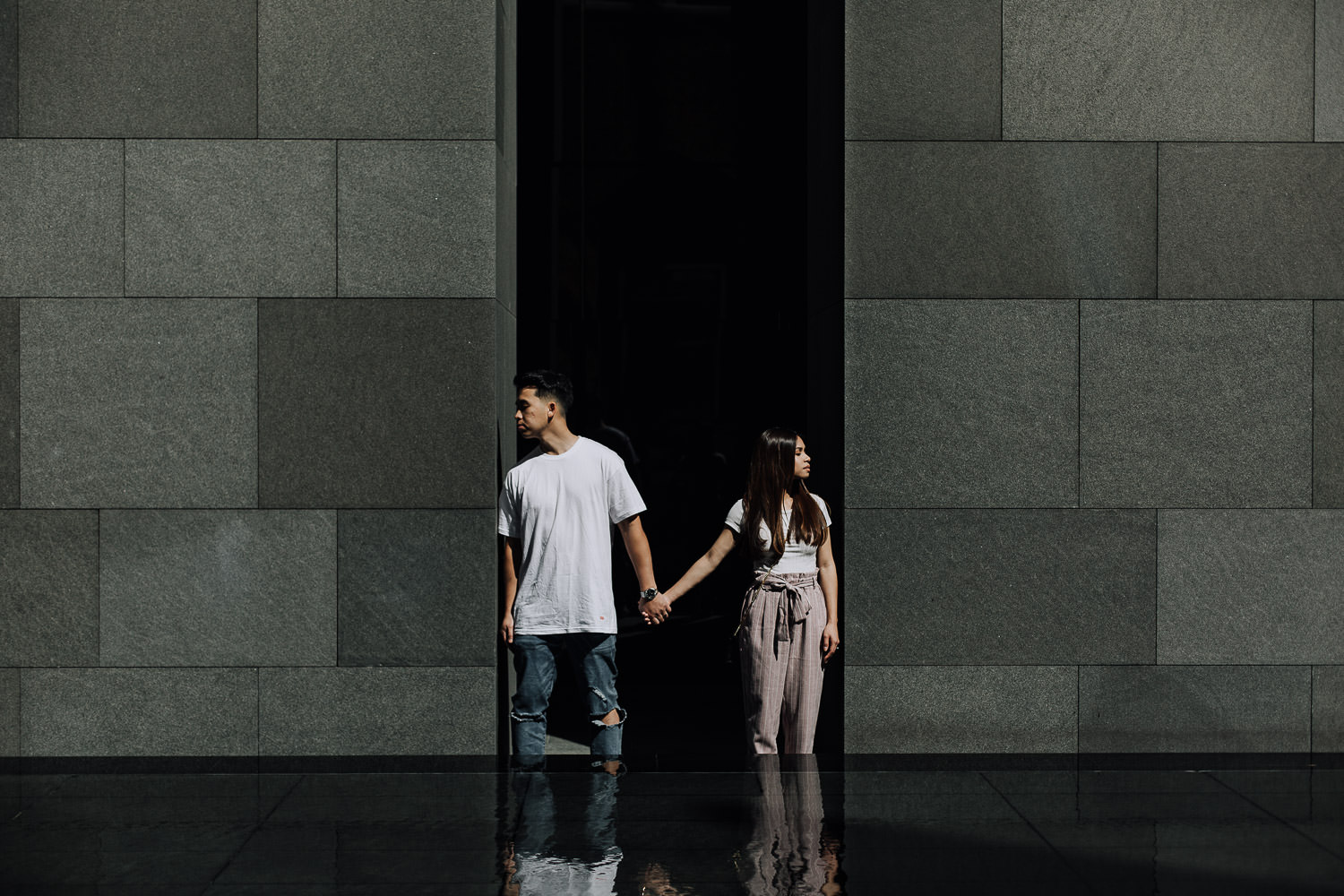 Couple standing in symmetry between granite walls