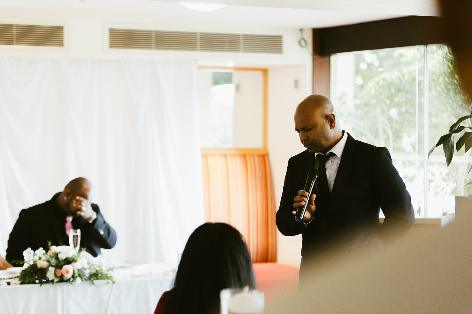 Father of groom trying to contain himself with the groom emotional in background