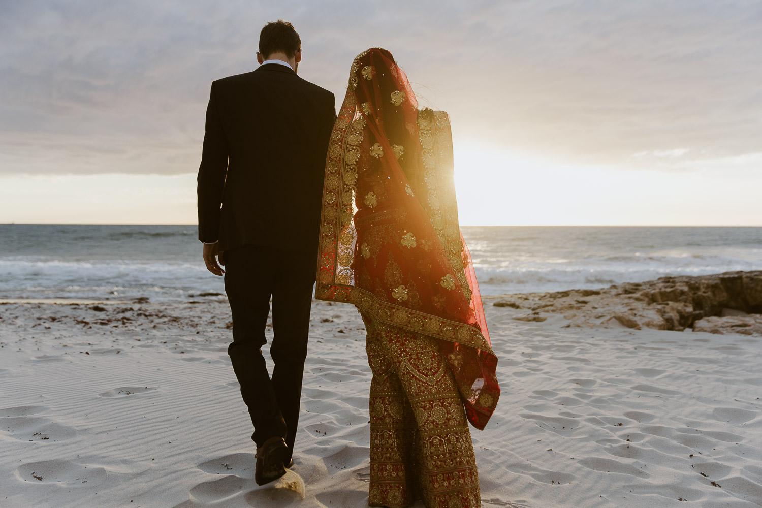 Indian bride and groom walking off into the sunset
