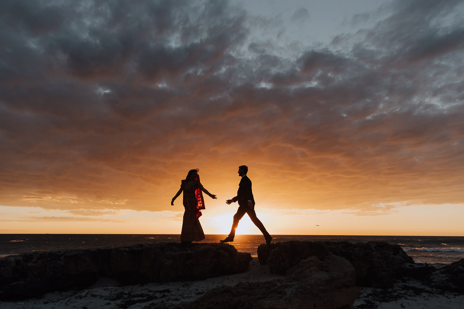 Groom leaping to his wife with sunset in the background