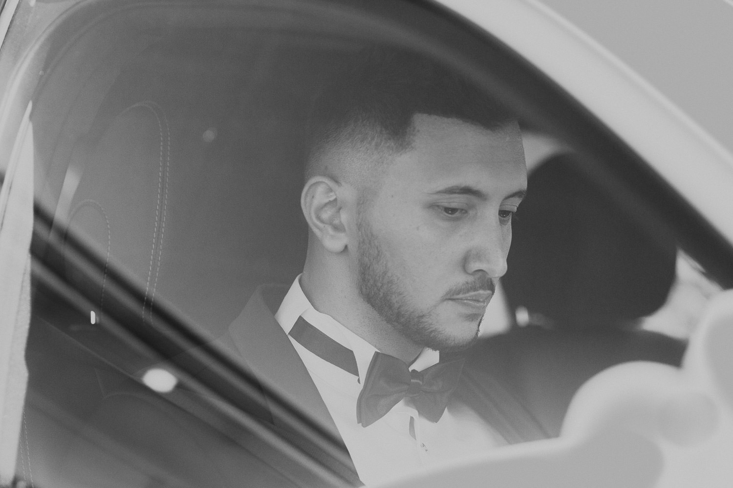 Groom getting in car to pick up her new bride