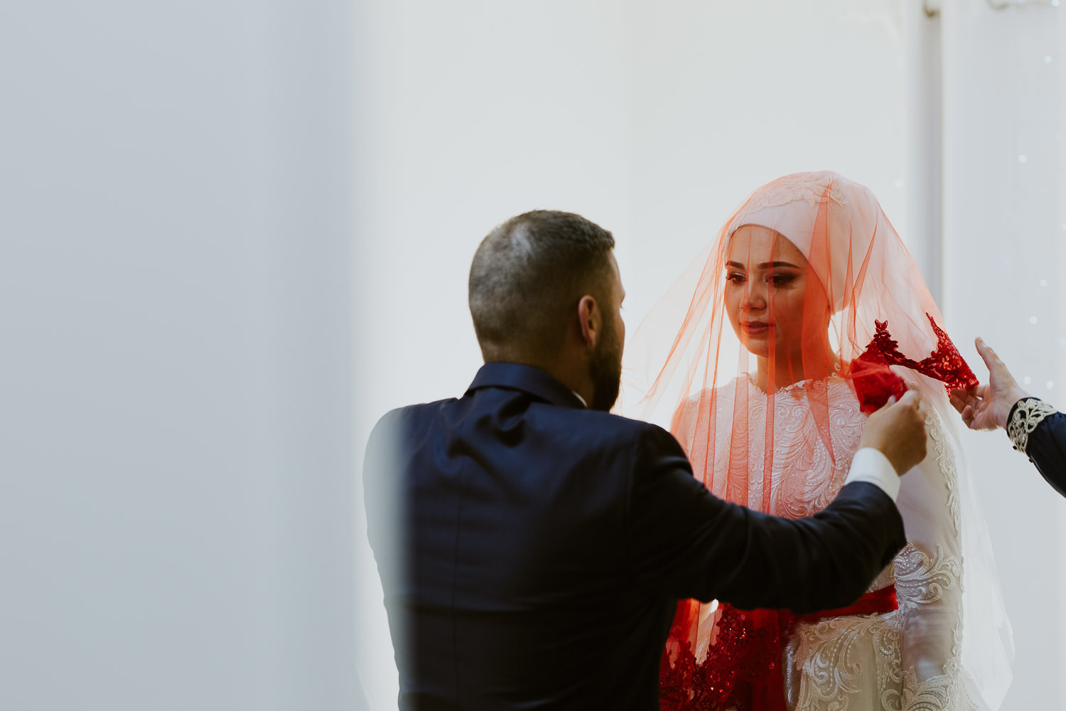 Brother covering her sister the bride with traditional red veil