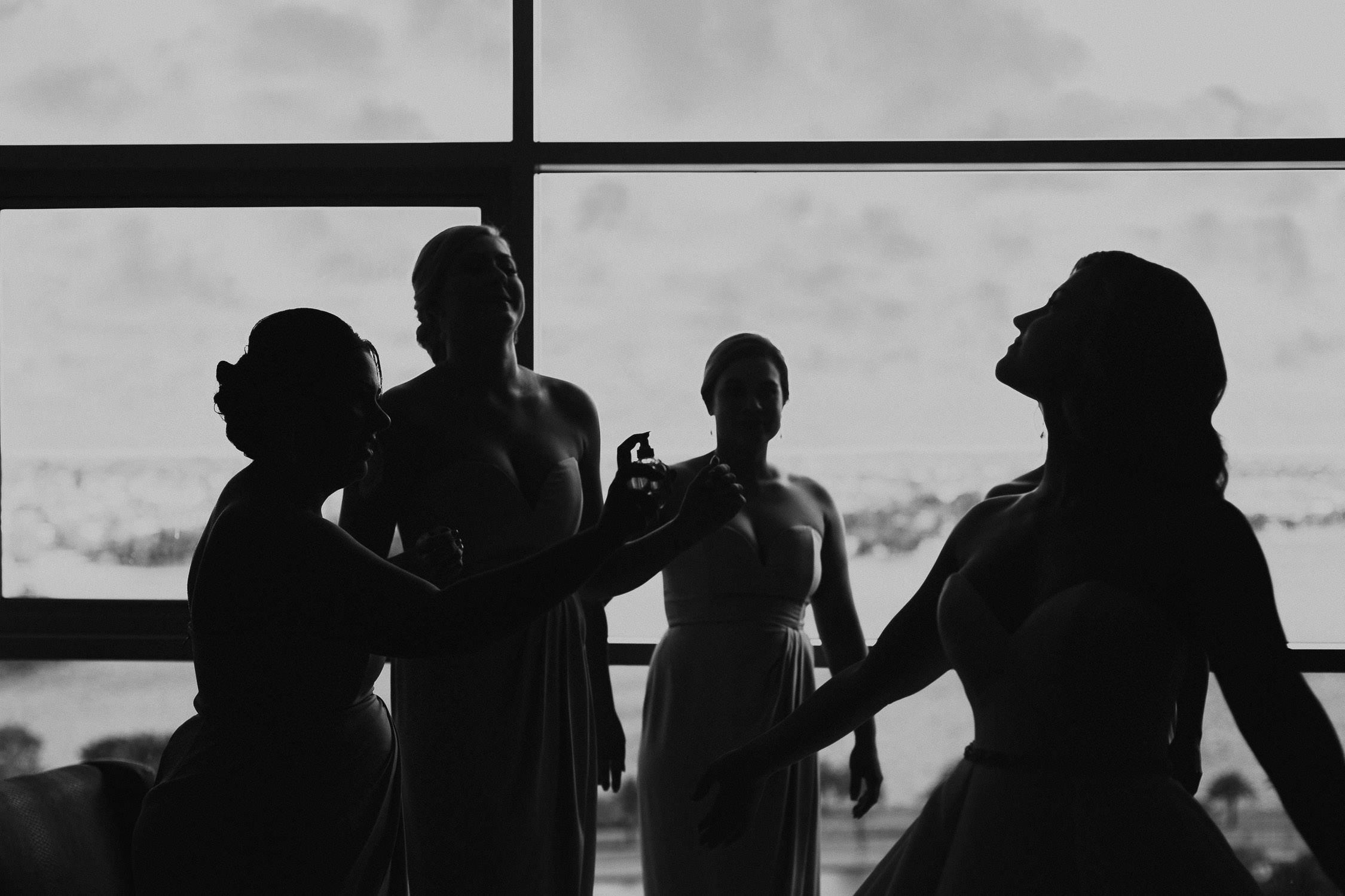 black and white image of bride walking thru spray of perfum with bridesmaids watching on at Fraser suites perth