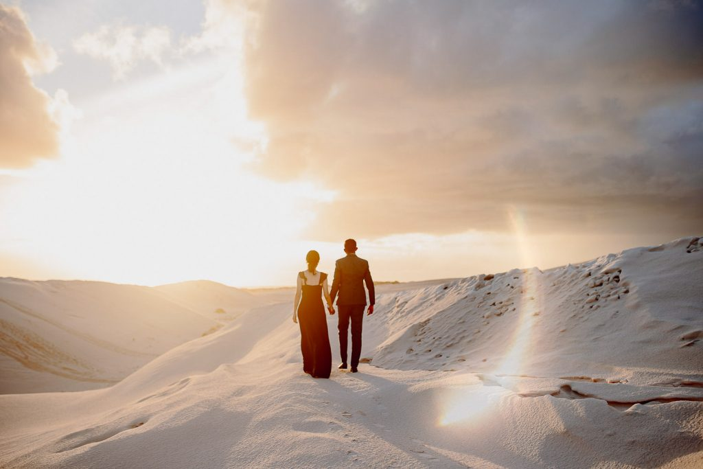 couple walking away together in lancelin sand dunes